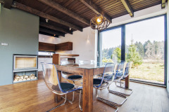 Interiér výberom materiálu i farebnosťou korešponduje s exteriérom. Prevládajú odtiene prírodného dreva doplnené antracitovým náterom kovových prvkov a kozubového telesa. Väčšinu vybavenia tvoria originály vyrobené podľa návrhu architekta, napríklad jedálenský stôl zo stropných trámov