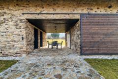 """Voľný """"prejazd"""" domom slúži ako krytá terasa na vonkajšie posedenie. Z oboch strán ho možno uzavrieť posuvnými drevenými vrátami a vytvoriť plne chránený priestor"""