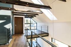 Vnútorné usporiadanie je úplne moderné. Drevený trámový strop a galéria nad spoločnou obývacou časťou akoby sa voľne vznášali v priestore. Strešnými oknami i oknom v štíte preniká veľa svetla