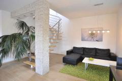 Manželia si vybrali otvorené oceľovo-drevené schodisko. Jeho vzdušná konštrukcia opticky zväčšuje priestor