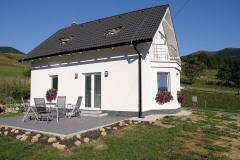 Dom má klasický tvar so sedlovou strechou a symetrické hlavné priečelie s balkónom (typ Ekonomik N7, dispozícia: 4+kk, úžitková plocha: 98 m2, mesačná splátka: 324 Eur)