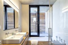 Do kúpeľní architekti navrhli hladké stierkové povrchy, ani tu nechýba prírodné drevo, na dlážke vyniká travertín