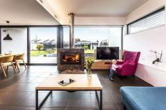 Obývacia izba sa vďaka posuvnému preskleniu otvára do záhrady. Hranicu pozemku uzatvára objekt so saunou a letnou kuchyňou