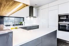 Minimalistická linka v bielej a šedej farbe s kuchynskou stenou až po strop. Pracovnú plochu osvetľuje horizontálne okno
