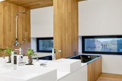 Základná kombinácia bielych plôch, prírodného dreva a čiernych prvkov sa opakuje aj v ostatných priestoroch vrátane kúpeľní