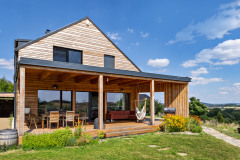 K najobľúbenejším častiam domu patrí veľká krytá terasa, využívaná ako vonkajšia obývacia izba. Zaujímavým prvkom je šikmá bočná stena s priechodom. Tvorí ochranu pred slnkom a vetrom, nebráni však výhľadom