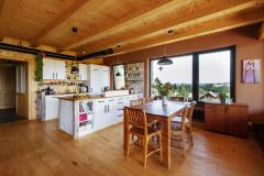 V spoločnej obývacej časti vyniká kuchynská linka z bielo lakovaných MDF dosiek s pracovnou plochou zo škárovky