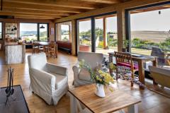 Aj v interiéri vládne prírodné drevo. Na stenách je kombinované s hlinenými omietkami. V hlavnom obývacom priestore sa, rovnako ako v celom dome, uplatnili výhľady a výtvarné cítenie majiteľky domu