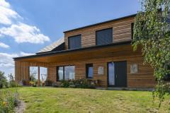 Fasáda má vetraný obklad zo smrekovcového dreva, ktoré časom získa prirodzenú patinu. Jeho sfarbenie kontrastuje s antracitovými okennými rámami, žalúziami a čiernu škridlovou krytinou
