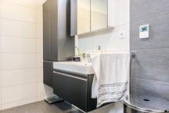 Dizajn kúpeľne sa nesie v kombinácii bridlicovo šedých a svetlých veľkoformátových dlaždíc, tomu zodpovedá aj zvolený odtieň kúpeľňového nábytku