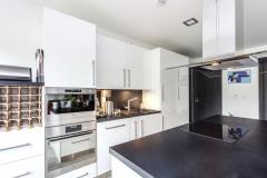 Kuchynský nábytok s povrchom v elegantnej bielej farbe s kontrastne tmavou pracovnou doskou doplňuje ostrovček s varnou doskou a digestorom v tom istom vyhotovení