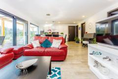 Pohľad do hlavnej obytnej miestnosti domu odhaľuje obytnú sekciu v popredí so sedacou súpravou, nasleduje jedálenský stôl pre celú rodinu a biela kuchyňa. V celom dome sú zvýšené dvere, aby vzduch ľahšie cirkuloval vo vnútornom priestore