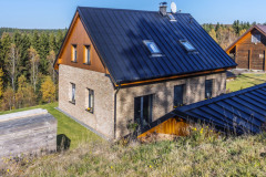 Dom je zasadený do nádhernej krajiny, v pravom rohu obrázku vidíte strechu záhradného altánku. Strechy sú pokryté plechovými šablónami – krytinou vhodnou v horách