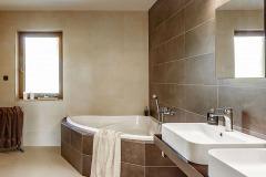 Priestranná kúpeľňa s rohovou vaňou v decentnej kombinácii béžových a hnedých veľkoformátových obkladov