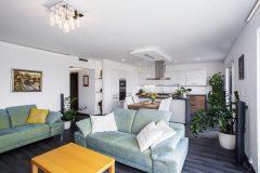 Obývacia izba s priestrannou kuchyňou je centrom domácnosti. Moderne zariadený interiér v prírodných farbách pôsobí útulne a návštevám sa často nechce odísť
