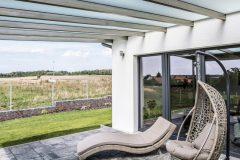 Priestranná vonkajšia terasa je zastrešená pergolou so špeciálnym sklom, ktoré je priesvitné, ale neprepustí ostré slnečné lúče a žiaru