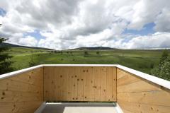 Balkón z masívnych drevených panelov, prístupný z rodičovskej spálne, poskytuje nerušený výhľad na okolité hrebene hôr
