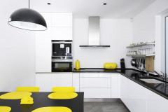 Čistá biela plocha kuchynskej linky zväčšuje malý priestor, jasné žlté akcenty oživujú neutrálnu sivobielu farebnosť celého interiéru