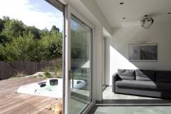 V lete je hlavná obytná miestnosť prepojená s terasou. Vďaka posuvným veľkoformátovým oknám tvorí nedeliteľný celok. Mólo sa zapustenou vírivkou predlžuje terasu do vnútra záhrady. Sibírsky smrekovec fasády farebne ladí s exotickou dlážkovou drevinou massaranduba použitou na vonkajšie povrchy