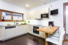 Rohová kuchyňa s príručným barovým stolíkom a dvomi barovými kresielkami s epedami