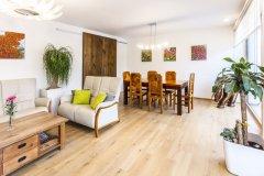 Hlavná obytná miestnosť domu s jedálenským stolom a sedacou súpravou. Posuvné dvere slúžia na praktické oddelenie kuchyne od zvyšku hlavného obytného priestoru