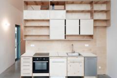 Box z preglejky obsahuje okrem kuchyne šatňu, technickú miestnosš, schodisko a pracovňu v podkroví s malou knižnicou. Pri dolnej spálni je k nemu pripojená kúpeľňa so sprchovacím kútom a samostatné WC