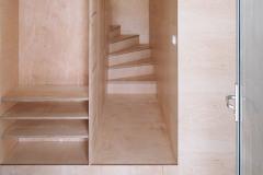 Pohľad na schodisko a šatňu z preglejky. Hoci ide o lacný materiál, pôsobí veľmi pekne. Architekti radi pracujú s kresbou dreva, ktorá na seba môže pekne nadväzovať