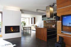 Medzi kuchynskou časťou a sedením je umiestnený atypický kozub s integrovaným osvetlením. Biele obkladové dosky sa krásne odrážajú od antracitovej veľkoformátovej keramickej dlažby