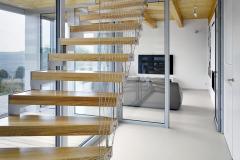 Krivočiare oceľové schodisko medzi prízemím a podkrovím je vyhotovené z oceľového plechu a tvrdého dreva. Má iba stupne bez podstupňov, konštrukcia sa kotví oceľovými kotvami do základovej dosky a do drevenej stropnice. Stupne sú z tvrdého dreva (jaseň), zábradlie tvorí lanková sieť