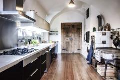 Pod historickou valenou klenbou a vedľa nádherne zrenovovaných starých dverí stojí moderná high-tech kuchynská linka