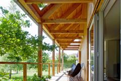 """Krytá terasa pozdĺž celej južnej strany domu v prípade pekného počasia slúži ako """"vonkajšia obývačka"""". Okno na presahujúcej streche je poistkou proti nedostatku denného svetla tak na terase, ako aj v interiéri"""