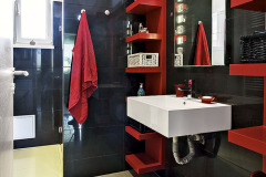 Vybavenie kúpeľne sa nesie v kombinácii čiernej a červenej farby, dlážku tvoria veľkoformátové keramické dlaždice