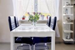 Jedálenský stôl je umiestnený pod oknom. Ako vidno, žalúzia nepustí do domu viac svetla, než je žiaduce