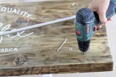 6. V spodnej časti dosky predvŕtajte dve tenké diery pre skrutky na uchytenie vešiaka