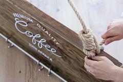 8. Cez vrchné diery prevlečte lano a ozdobne ho na koncoch uviažte. Na vešiak zaveste háčiky a šálky
