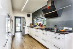 Kuchynská linka je vyrobená z bielych lakovaných MDF dosiek (Sokol Interiéry), stena pri okne je obložená sklom
