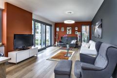 Spoločnú obývaciu časť domu tvorí priestor so sedením, jedálňou a kuchyňou. Jeho súčasťou je veľké akvárium, splnený sen domáceho pána. Majitelia majú radi prírodu, preto do obytných miestností zvolili lepenú drevenú dlážku vo vyhotovení patinovaný dub. Krásne s ňou ladí farebná kombinácia sivej, bielej a tehlovočervenej farby, ktorá pôsobí harmonicky a nie nudne
