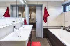 Na poschodí sú dve kúpeľne, s vaňou a so sprchovým kútom. Aj sem prenikla kombinácia sivej, bielej a čiernej farby s prírodným drevom.