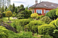 Pohľad na rodinný dom cez jazierko, v okolí ktorého sa nachádzajú hlavne kosodreviny. V pozadí tvarovaná borovica čierna (Pinus nigra Austriaca) a starostlivo tvarované tuje